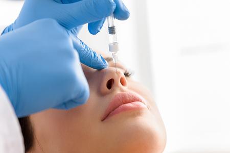 Artsenhand die in gezicht van kalme vrouw inspuiten Stockfoto - 78447225