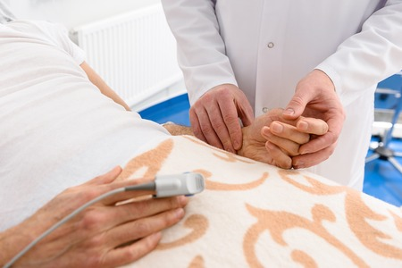 Physician keeping hand of ill male Stock Photo