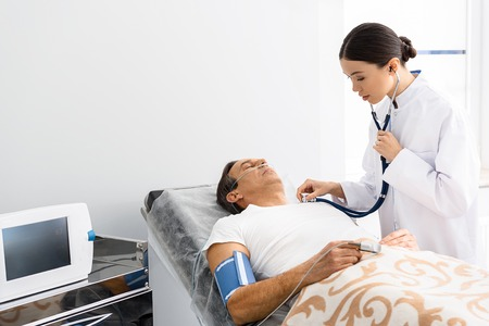 Calm female doctor listening male by stethoscope
