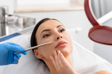 Calm girl watching at reflexion in surgery room Stock Photo