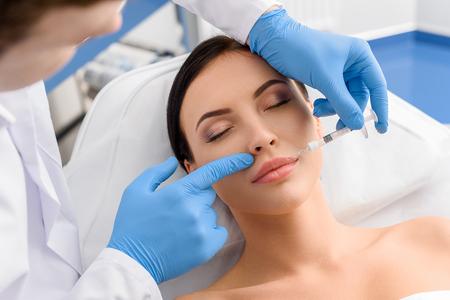Tevreden vrouw die injectie in gezicht ontvangt Stockfoto