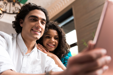 Excited guy and girl using modern technology Stock Photo