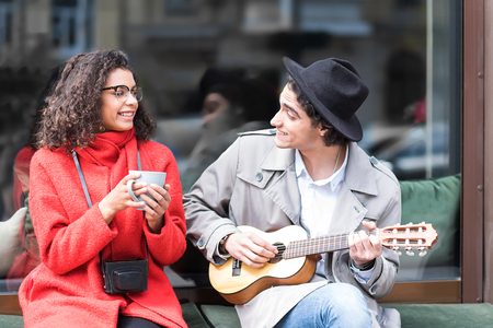 Cheerful loving couple enjoying music outside the cafeteria