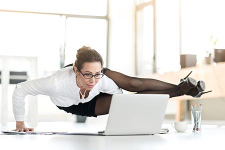 Glückliche Frau macht Übungen während des Arbeitstages