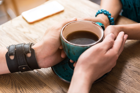 Let me warm your hands by my love. Close up of young man and woman keeping hands on cup of coffee. They are sitting at table Stock fotó
