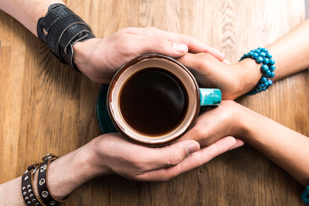 Top view close-up of hands of loving couple holding cup of coffee together over the table Stock Photo