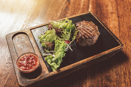 Appetizing juicy meat with lettuce and spicy dressing