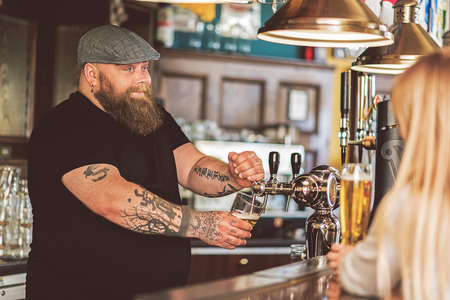 Cheerful bartender filling mug of cold lager in pub