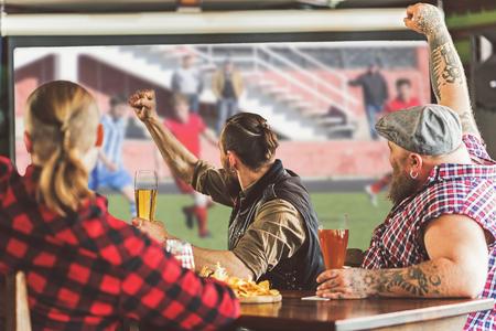 Vrolijke volwassen mannen drinken bier in de bar Stockfoto