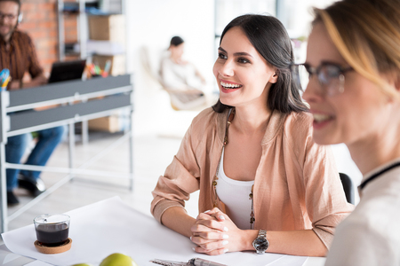 Cheerful smiling female coworkers in office Stock Photo