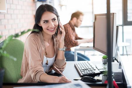 keyboard: Happy smiling female worker talking at phone