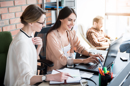Jolly concentrated women working in office Stock Photo