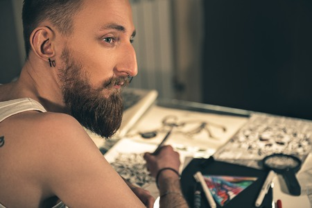 thoughtfulness: Pensive bearded man creating pictures
