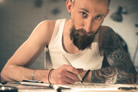 Thoughtful bearded man painting picture