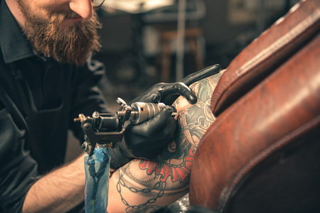 thoughtfulness: Tattoo machine doing image on hand of woman Stock Photo