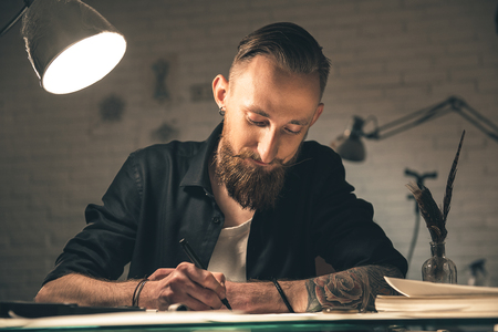 Happy bearded male creating pictures at table
