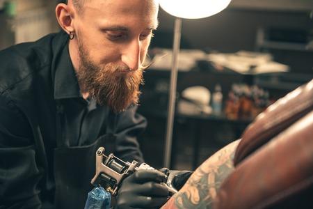 thoughtfulness: Serene bearded man making tattoo