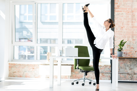 Outgoing woman stretching legs at job