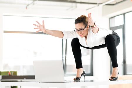 Cheerful female doing gymnastics at job