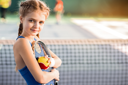 Cheerful female kid playing tennis with enjoyment Stock Photo