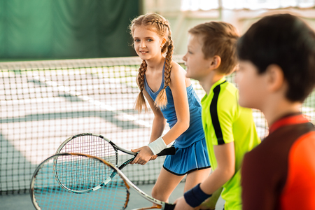 Joyful kids having fun on tennis court