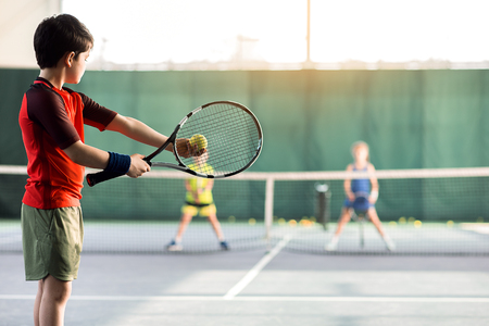 Cheerful kids playing tennis on court