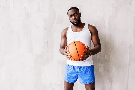 Deep looking bearded athlete standing by wall with basket-ball in arms