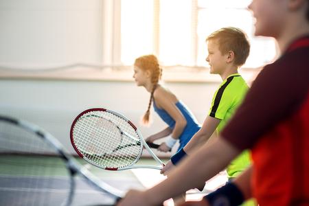 Los alumnos felices disfrutando de tenis juego Foto de archivo - 79182777