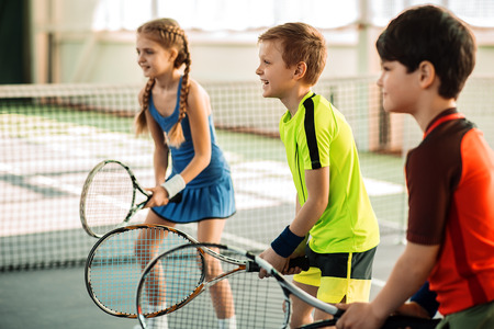 Happy girl and boys playing tennis