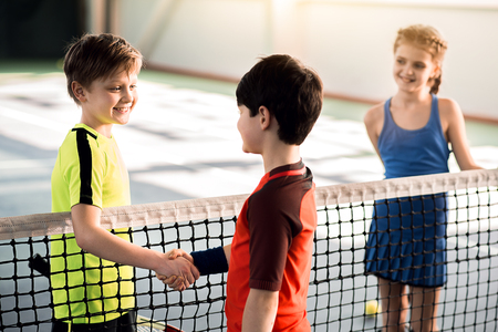 Vrolijke jongens die handen schudden alvorens tennis te spelen