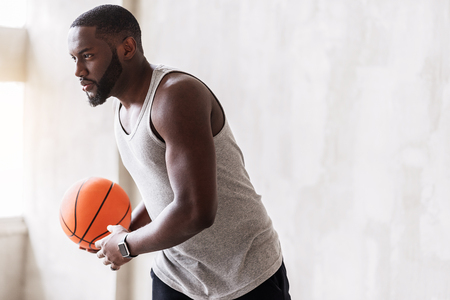 Jolly african bearded sportsman training with basket-ball