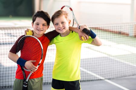 테니스 코트에서 즐거운 행복한 아이들 스톡 콘텐츠