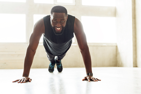 Cheerful african sportsman performing power load exercises