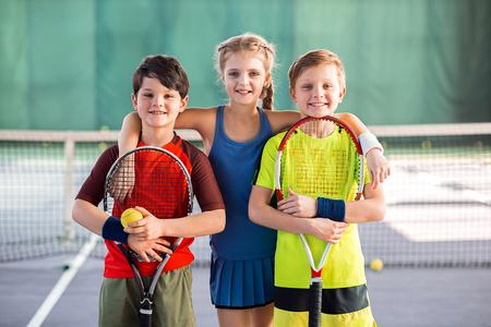 Bambini allegri divertirsi nel campo da tennis Archivio Fotografico