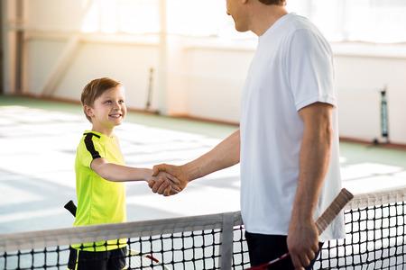 Proud tennis couch praising his pupil