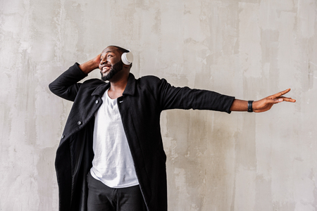 Jolly handsome african trendy man having fun listening to music