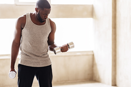 Severe african bearded sporty guy making power exercises