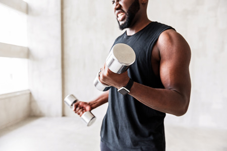 Angry bearded sportsman making muscle-building exercises