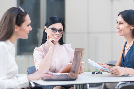 Thoughtful woman telling with smiling associates