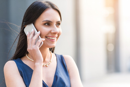 Happy woman telling by phone