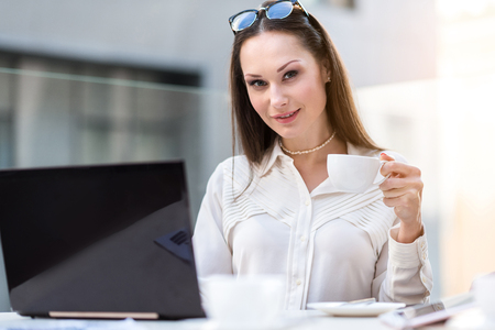Outgoing woman drinking cup of delicious coffee