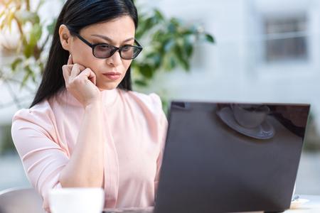 Pensive female watching at laptop