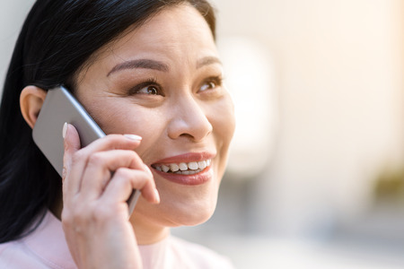 Cheerful woman speaking by mobile Stock Photo
