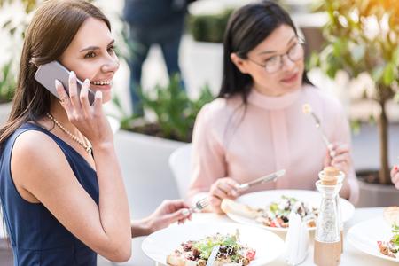 Cheerful female talking by phone