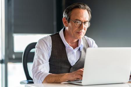 Thoughtful senior businessman typing on notebook Stock Photo