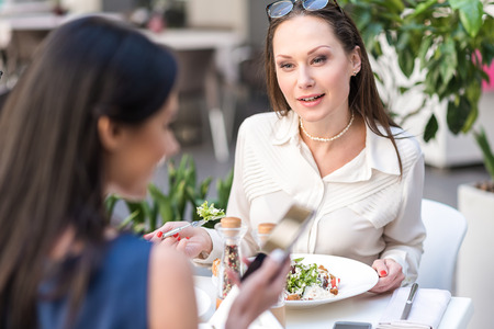 Interested woman tasting salad in cafe