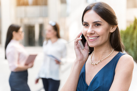 Cheerful woman telling by phone