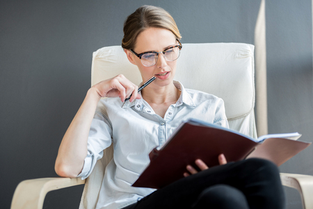 Attractive pleasant lady holding journal pensively