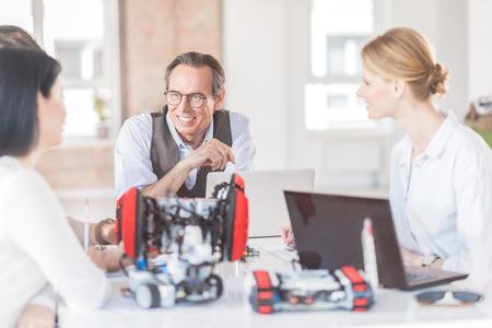 Ingenieros positivos creando robot en oficina Foto de archivo - 79317827