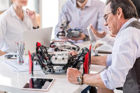 Grupo de inventores que construyen dispositivos en la oficina Foto de archivo - 79317832